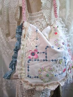 Charming vintage embroidery bag with sweet little embellishments. This bag is handmade with vintage linen. The linen has floral embroidered heart shapes. Ive added colorful little buttons and snippets of vintage lace. The strap is braided cotton. The lining is a mix of soft cotton prints. There is a large interior pocket. This bag has a flap closure. Overall, bag is light in weight. Makes a wonderful summer outfit bag! NOTE: This is an eco-friendly creation handmade with vintage and upcycled…