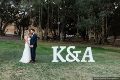 Couple photography in front of large initial signs, string lights hanging from trees