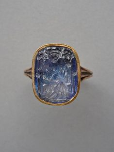 Intaglio; sapphire; beardless personage (Duc de Berry?), wearing hat and long robe, seated facing in chair with foliated ends to the arms and back; mounted in modern gold ring - 15thC(early). | © Trustees of the British Museum