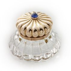 A Faberge gold and rock crystal inkwell, the lobed rock-crystal body carved with bombe' sides, the hinged gold cover also lobed and surmounted with a cabochon sapphire, marked Faberge' with workmaster Michael Perchin's initials, 56 standard, circa 1890.  Gross weight 60.84 grams.  60,000 pounds sterling  - Bentley & Skinner