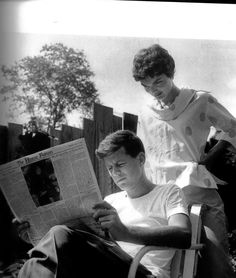 Jack reads the paper while Jackie looks over his shoulder. May 1954