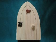This sweet fairy door  kit comes with a dragonfly decoration, hinge and screws and a door handle, it is made of pine and padauk. You can paint it, stain it or do decoupage to make it your own It was created by scroll saw artist Joanne MacKenzie