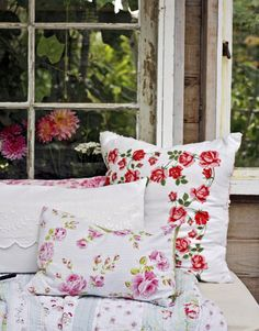 Lush, feminine florals and remade castoffs lend a homey feel to the interior of the one-room hideaway. Here, flower-strewn linens get new life on pillows.