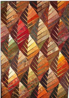"""Nouveau Leaf. (Art Quilts by Betty Busby) Tessellated leaf shapes in carefully shaded autumn colors fill this quilt.  It's equipped with a hanging sleeve for wall display or it can be used on a bed.  The stitching is done in a spiral pattern using variegated thread.  58.5x83"""""""