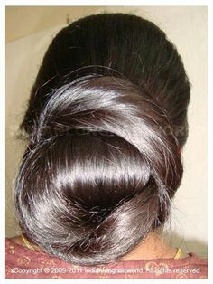 What a beautiful low bun ! Care however should be taken before adopting such hairstyles, as due to it's high static charge, it will cause phlegm to move up in the throat, causing the voice to quaver & a frequent urge to clear the throat. A heavy chabi chhalla with a long & wide hook if inserted at the edge of the pleats of the saree, will reduce this problem as it's hook will activate the acupressure points that act to keep the throat clear.