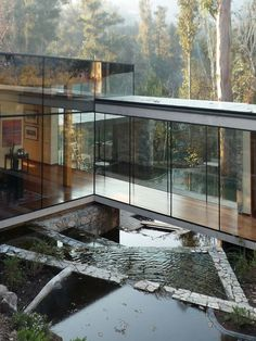 Glass stone and water. Bridging element, frameless glazing in woodland