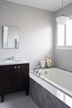 The use of the same color with different shapes. Monotone color and playing with texture and geometry. Also like the bit of thin back splash around the tub that matches the vanity top.