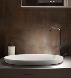 A semi-recessed sink with a delicate shape with its semi-rolled rim made with SculptureStone™.