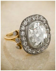 Gold and platinum engagement ring with a 4.04 carat antique cushion cut center diamond.