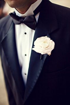 Very formal and classic groom's attire. Black and white with bow tie and a single rose boutonniere