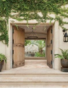 this courtyard entry - that chandelier, Spanish stone, aged wood doors, black hardware & vines.