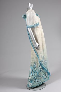 Ramon Valera sequined and beaded gown or `Terno', Philippines, 1960s, the iridescent sequined ground adorned to the hem with blue and white sequins and beads in swirling Paisley motifs, with babarahin stiffened `butterfly' sleeves and gauze over-panel edged in blue beads and droplets, rosettes to the shoulders Baro't Saya, Barong, Filipiniana, Beaded Gown, Blue Beads, Filipino, Rosettes, Iridescent, Philippines