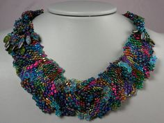 A freeform peyote necklace by Dina Broyde, stitched front with tubular netting in the back. Colors varying from greens to pink, violet, and gold. Embellished with leaf & flower forms.