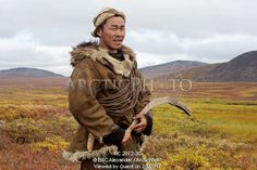 Image of sasha takui, a chukchi reindeer herder, working with his reindeer at their autumn pastures. he is holding a curved throwing stick (kenunen), which he uses to change the direction his reindeer are going. it is similar to a boomerang. iultinsky district, chukotka, siberia, russia by ArcticPhoto