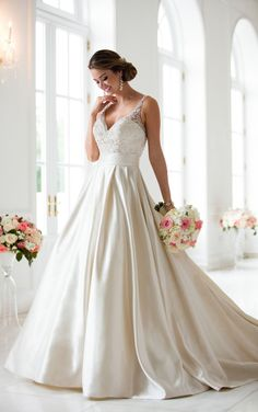 This ball gown with sash wedding dress from Stella York is full romance! Dolce satin creates a stunning silhouette from beaded straps and sweetheart neckline to voluminous skirt. Linear beading highlights the neckline while a satin sash at the waist flattering the figure.  Pockets give this dress a modern update. This satin ball gown is available in plus sizes.
