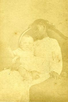This photo is so faded as to nearly have disappeared. If it were mine I would look into restoration because this seems an unusual one. A very young (dead) black girl, and a giant headed white baby. Is the baby dead? Is its arm moving, or is that an illusion because of the fading? Is the girl the baby's mother? What year is this?