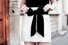Black bow on white mini skirt.