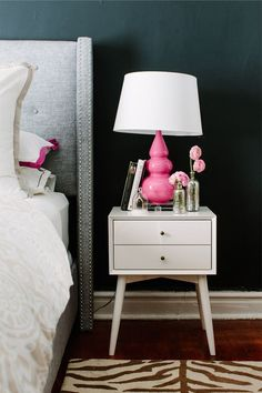 Feminine bedroom with pink glass table lamp on top of a white nightstand and upholstered gray wingback headboard
