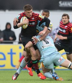 Owen Farrell of Saracens is tackled by Luther Burrell and Christian Day during the Aviva Premiership semi final match between Saracens and Northampton Saints at Allianz Park on May 12, 2013 in Barnet, England.