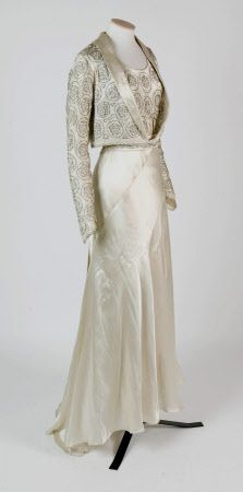 Cream satin dress, the bodice and jacket embroidered in bugle beads. Part of wedding dress with SPR/DR/2047B.