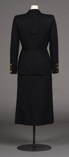 Day Suit  DesignerAdrian, Gilbert  BrandAdrian  Date1948  Year Range from1948  Year Range to1948  MaterialCotton suiting, brass disks & rayon faille lining  Credit LineGift of the Fashion Institute of Design & Merchandising  CollectionPermanent Collection