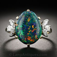 A no less than spectacular black opal, modeled in a slight egg shape and glowing with a hypnotic palette of electric confetti - blue, green, red and orange - is elegantly presented between sparkling flares of pear shape and marquise diamonds in this superb and stunning jewel, finely crafted by the eminent American jeweler - Raymond Yard.