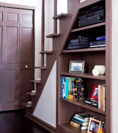 entertainment center under stairs | dark hardwood staircase beside built-in bookshelf
