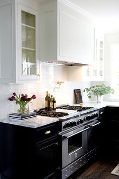 classic kitchen with white upper cabinets and black lower cabinets marble countertops and a white subway tile backsplash. beautiful ideas. Home Design Ideas