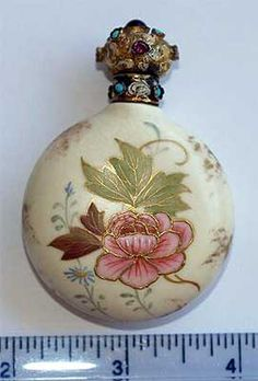 Exquisite Austrian Gilt Porcelain Perfume  An ornate gilt silver and enameled hinged lid is adorned with genuine almandine garnets or rubies and is fully hallmarked with both Austrian control and maker marks. The body is a delicate, hand painted porcelain in a foliate design with raised gold enameling. Very good condition, c. 1900,