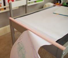 Using a piece of trim on Latt table to hold down paper and create a clean tear.