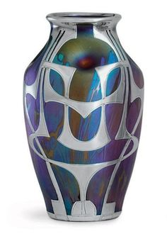 A BOHEMIAN ART NOUVEAU SILVER-MOUNTED GLASS VASE, LOETZ, CIRCA 1902. Ovoid, the iridescent turquoise, purple and green glass applied with silver strapwork, the glass and mounts apparently unmarked.