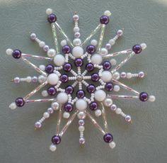 Korálková+hvězdička+s+fialovými+perlami+velká+Hvězdička+je+vyrobena+z+korálků+bílé+a+fialové+barvy.+Je+na+pevné+drátěné+konstrukci.+Velikost+hvězdy+cca+10+cm.+Hvězdička+se+hodí+pro+sváteční+výzdobu+Vašeho+bytu+nebo+může+posloužit+i+jako+malý+originální+dáreček.