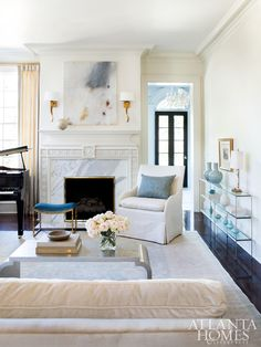 In the living room, an Oushak from Moattar anchors the space, while Porta Romana's wall sconces and Giacometti stool, and a matte gold fire screen, add subtle glamour.