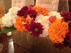 "Her stunning arrangements set the fall color palette. ""I fill gold rectangular vases with an assortment of flowers in fall colors — off-whites, burnt oranges and cranberry,"""