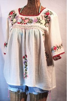 Mexican style embroidered peasant blouse with cutoffs (and an odd wicker body).
