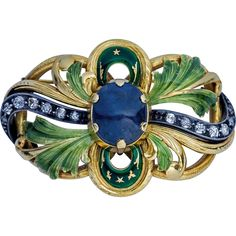 An original antique Art Nouveau partially enameled openwork gold  silver brooch / pin, circa 1915, centered with a large cabochon cut sapphire