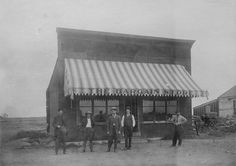 Exterior view of men standing in front of the Bargain Store in San Fernando, circa 1900-1920. The store was owned by Joe Iverson (second from left). Chatsworth Historical Society. San Fernando Valley History Digital Library.