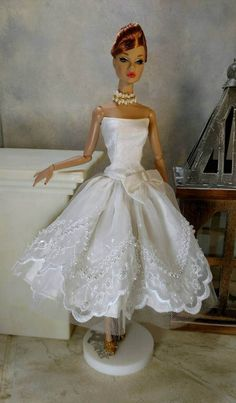 This white organza and white silk dress features tiny white pearls, clear sequins and white embroidery. Two layers of tulle soften the look and a bow at the side waist tops off the look. Lined in white silk. Corset closure for a snug fit. From a smoke and pet free home