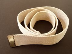 This vintage 1980s military belt is beige webbing and one end has a brass cap. There is no buckle - a replacement for your worn out webbing! Will fit up to a 34 inch waist.  It is 36.75 inches (93.3 cm) long and 1.25 inch (3 cm) wide. Very good condition. End cap is scratched. It has been washed.  You can see more belts here: http://www.etsy.com/shop/bytheway?section_id=6301102  Thanks for looking! I am happy to answer questions! Jaci ByTheWay.etsy.com  This belt now resides in a…