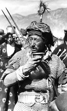 Tibet armor, riveted mail hauberk with mirror armor, steel helmet, armored belt. Tibet, New Year's Parade, 1938 / 1939. Comments:Note the arrow tail ends sticking out above his shoulder on the right side of the picture. These festivities included shooting a bow and musket from a horse.
