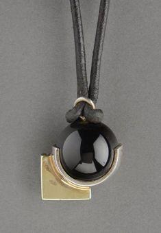 JEAN DESPRES (1889-1980). Collier à monture Art Déco en or et argent enserrant une sphère en onyx noire. Poinçon de l'orfèvre et poinçons tête de sanglier et d'aigle. Vers 1930. Poids brut: 20 gr