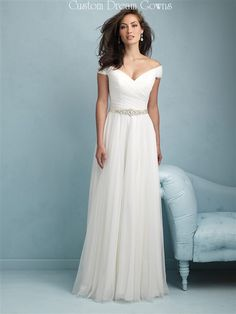 Graceful Soft Tulle A-Line Gown with a V-Neckline, Off Shoulder Cap Sleeves, Ruched Criss-Cross Fitted Bodice with a Crystal Beaded Satin Band at Natural Waistline, Gathered Tulle A-Line Skirt, Chapel Train, V-Back with Covered Buttons to Hem and Hidden Zipper Closure. #offshoulder #weddingdress #tulleweddingdress #alineweddingdress #bridalgown #capsleeve #romanticweddingdress #receptiondress #destinationwedding #beachweddingdress #crystalbelt #weddingfashion #weddingstyle