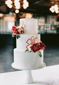 A marbled wedding cake in white, red and rose gold.