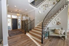 This beautiful spiral staircase spans all four floors of this amazing home.  Intricate iron railings add an exquisite look to the already amazing staircase.  Picture wall up the first flight of stairs.