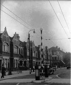 Fulham Palace Road junction with Kingwood Road. Note Trolleybus overhead lines and white blackout rings on lampposts, and person with gas mask. Vintage London, Old London, Fulham, Fair Lady, London Photos, Old City, Back In The Day, London England, 1940s