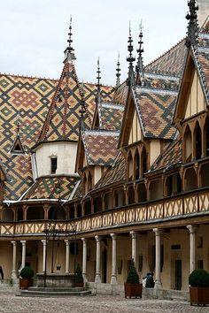 L'Hôtel-Dieu, avec ses façades gothiques, ses toits vernissés, tapissés de figures géométriques aux couleurs flamboyantes, fait partie du patrimoine des Hospices de Beaune, institution charitable créée en 1443 par Nicolas Rolin, chancelier du Duc de Bourgogne et son épouse Guigone de Salins.