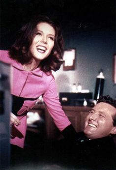 Diana Rigg as Mrs. Emma Peel, and Patrick Macnee as John Steed, have a laugh between takes of  'The Avengers' in 1965