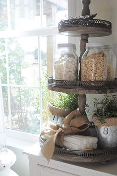 for bathroom: put cotton balls, q-tips, bath salts, oatmeal face scrub, wash cloths on bottom, votive candles on top or perfume bottles.  Luv it for a guest bathroom!