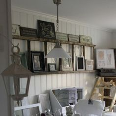 7 Unique Ways to Decorate using a #wooden #Ladder -  used here as a shelf to display a collection of frames on a wall.