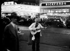 A strolling blind musician plays guitar and harmonica along Broadway at night in Times Square in 1944